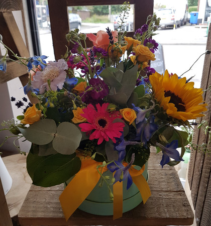 A bright and cheerful selection of seasonal flowers, beautifully arranged in our Medium  Hatbox. (Please note that we will use seasonal flowers and content might therefore be slightly different to the photo).