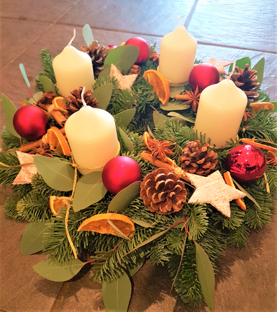 Our Traditional Advent Wreath is installed on a floral foam base, with a selection of fresh festive foliages and scented accessories, and gorgeous baubles. It comes supplied with 4 Church style candles, one to be lit on each of the Advent Sundays.  If you prefer different colourways please let our team know. We want to make it bespoke for you...