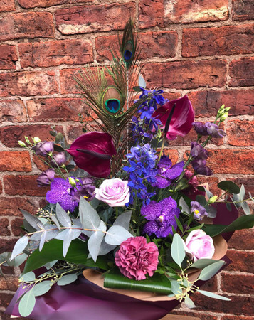 Our Juno Bouquet, in Moody Blues. is an absolute show stopper.  Why Juno? Juno was the Roman Goddess of Women, Love and Marriage and her symbol was that of a Peacock. We use Peacock feathers within this bouquet and base the rest of the flower pallet on the Peacock's amazing colour scheme. We include extra-special Vanda purple orchids, exotic Anthuriums and these are complemented by Blue Delphiniums and dusky pink flowers.  Please allow a minimum 48 hour notice period for delivery when selecting this very special bouquet.