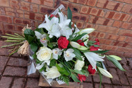 A handtied sheaf is a traditional and natural looking gesture, often selected as a Funeral tribute.   The image shown is red and white but we can of course prepare to any preferred colour scheme, do feel free to contact our friendly and sympathetic team who will be able to help you.
