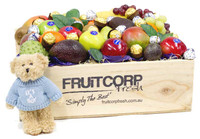 "Beautiful Baby Boy Arrival Gift Hamper. It comes in a hand crafted wooden Gift box that is filled with Ferrero Rocher Chocolates, Baci Chocolates, Fresh Seasonal Fruit and a very cute little Message bear that is wearing a blue jumper with ""It's a Boy"" written on it."