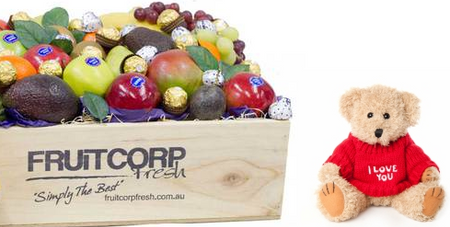 A beautifully presented fresh fruit hamper in a wooden box with a cute, little and soft I love you message teddy bear and baci and ferrero rocher chocolates.