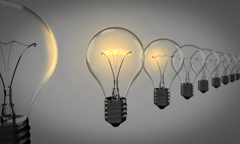 Illuminated light bulbs against sky