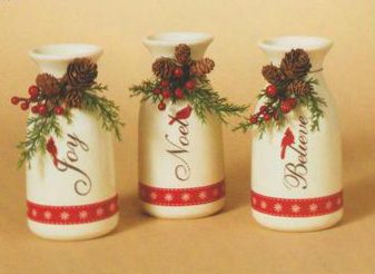 "Three 6"" ceramic holiday milk bottles with floral accents and holiday sentiment written on side: Joy, Noel and Believe. Comes boxed."