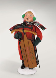 The Snow Day Kid with Sled is bundled up snug and tight and is ready to have some fun.