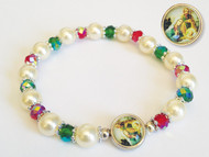 """7"""" Christmas stretch bracelet with enameled nativity medal. 8mm imitation round pearl beads with a 6 mm red and greeen multi faceted aurora borealis finished crystal beads. Comes with  a gold stamped holy prayer card included."""