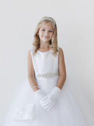 This ankle length communion dress has a satin bodice is attached to a tulle skirt. The buttons down the back of the dress are covered with satin. Satin covered buttons down the back of dress.