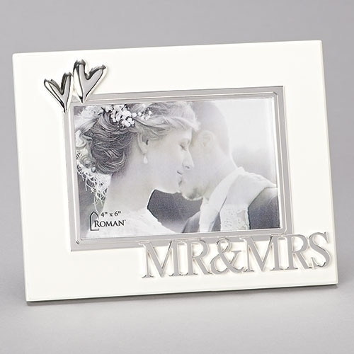"""7""""H White Wedding or Anniversary Photo Frame adorned with decorative hearts and the words Mr. and Mrs. across bottom of the frame.  Frame holds 4"""" x 6"""" photo. Frame is made of sturdy medium density fiberboard."""