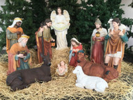 Large Nativity set with the Holy family, the three wise men, the angel, the shepherd, and three animals in some hay.