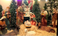 Life-size Nativity set with the holy family, the wise men, the shepherd, the angel, and some barn animals displayed on hay.