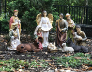 Large Nativity set with the Holy family, three wise men, shepherd, angel, cow, donkey, and sheep, displayed outside.