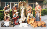 Life-size Nativity set with the Holy family, three wise men, shepherd, angel, cow, donkey, and sheep, displayed outside.