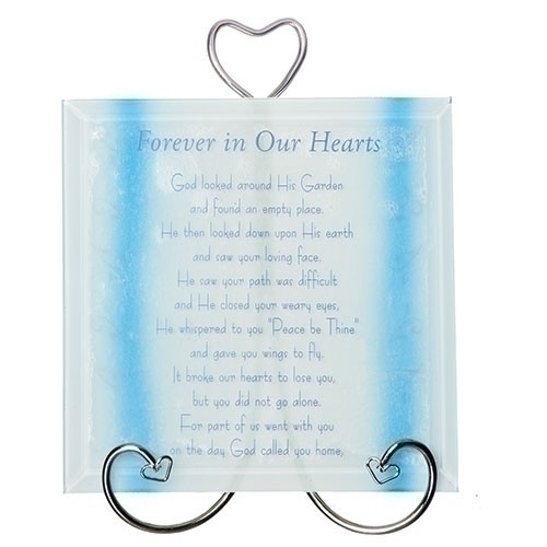 """Forever In Our Hearts Memorial Plaque with Stand. The Forever in Our Hearts Memorial Plaque measures 5.75"""" x 4.75"""".  The words on the bottom of the Memorial Plaque say """"God looked around His Garden and found an empty place. He then looked down upon His earth and saw your loving face. He saw your path was difficult and He closed your weary eyes. He whishpered to you """"Peace be Thine"""" and gave you wings to fly. It broke our hearts to lose you, but you did not go alone. For part of us went with you on the day God called you home."""" Made of beveled blue colored glass."""