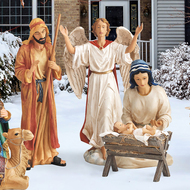 Metal Nativity set with Joseph, Mary, baby Jesus, and the angel, displayed in a yard.