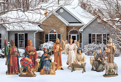 Metal Nativity set with the Holy family, three kings, angel, two shepherds, and animals displayed in a yard.
