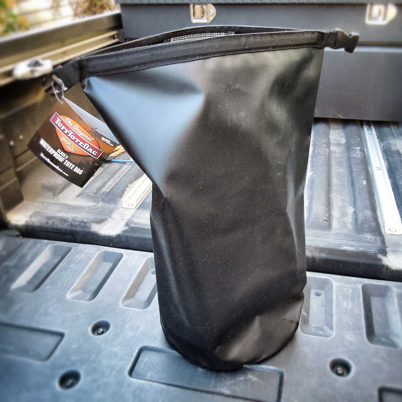 Back view of the rolled open Tuff Tote bag handle, handle rolls up to open the black waterproof Tuff Tote bag.