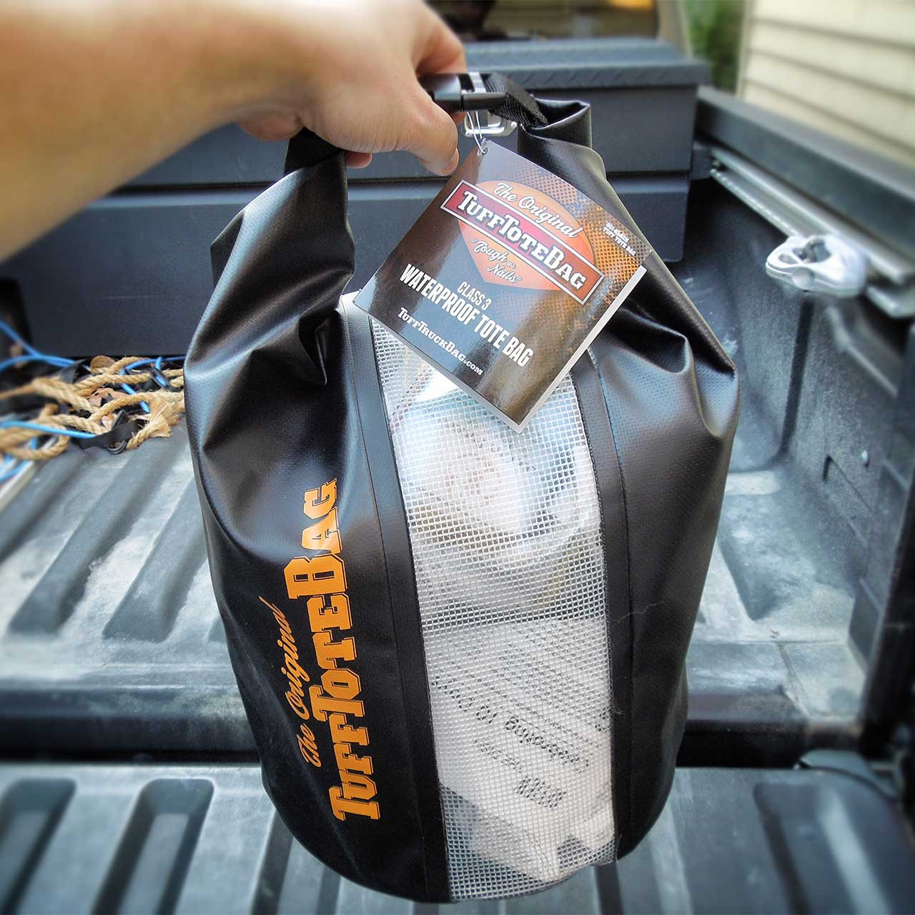 Demonstration of how the roll-to-clip handle works on the class three waterproof black Tuff Tote bag.