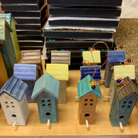 brown standing bird house in the back of left row of 3 birdhouses is sold