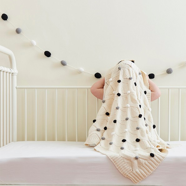 Monochrome-pompom-baby -blanket-with garland