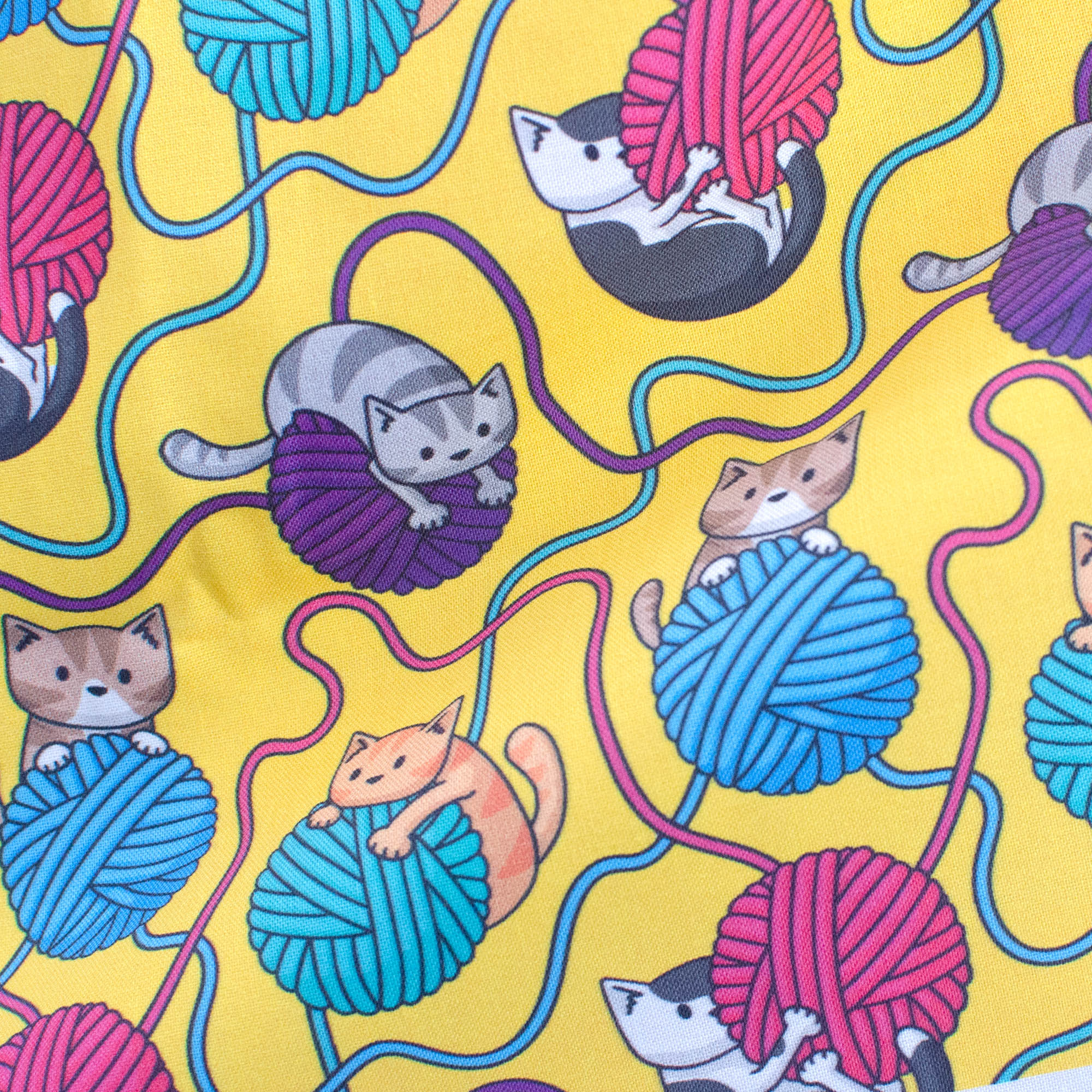 Doodlecats and yarn on yellow fabric