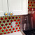 Mini Kyle knob complements colorful kitchen glass back splash and white cabinetry
