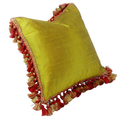 Lido pillow is double sided covered in nugget green silk and surrounded by gold and red tassel trim. The flip side is woven fabric with chevron weave in vibrant red.