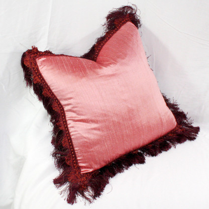 Baja pillow in rosy pink silk surrounded by fringe in burgundy and metallic threads.
