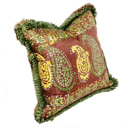 Casbah pillow mocha is covered in a silk print with a  paisley pattern in yellow and spruce green surrounded by lush fringe.