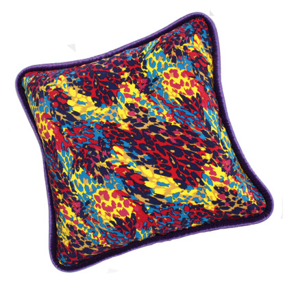 Cabo Pillow covered in splashy colorful printed silk and trimmed with velvet piping