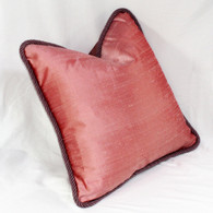 Baja pillow with twisted cord trim is covered in a rosy pink dupioni silk.