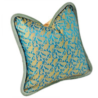 Java pillow is covered in silk print with golden paisleys on shimmering turquoise background.