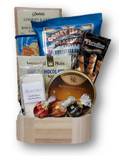 This snack basket has a selection of chocolates, cookies, nuts and candy.
