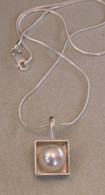 fresh water pearl set in a sterling silver box hung on a sterling silver snake chain