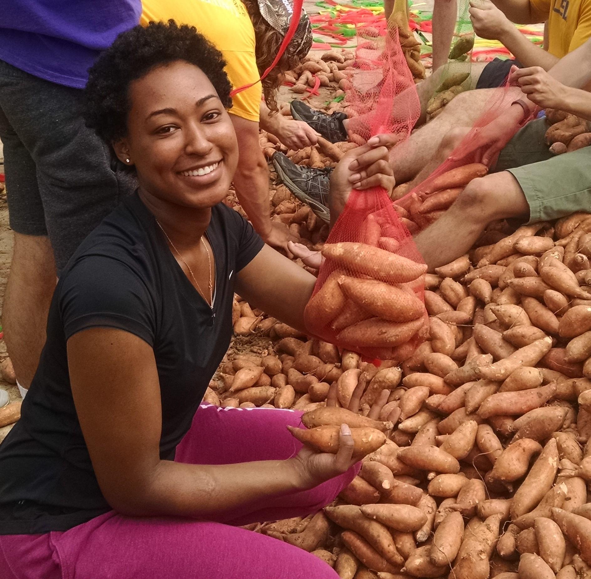 Volunteer holding a bag of Sweet Potatoes