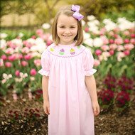 Girls cupcake smocked bishop dress with different shades of purple cupcakes topped with sprinkles and a cherry.
