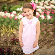 Monogrammed pink lined dress has a rounded neck with white piping and a white hem.