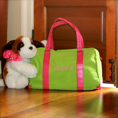 Large monogrammed lime green with pink trim travel bag has comfortable handles and a shoulder strap.