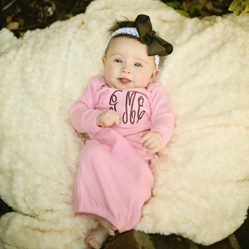 Monogrammed pink baby gown in the Monogram Script font with brown thread.