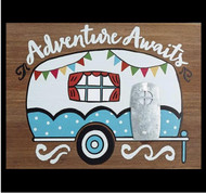 Hand painted wood sign that has a camper with the saying Adventure Awaits.