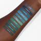 blue and green lipstick swatches on dark skin