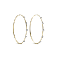 """Diamonds sprinkled around an endless hoop with ILA's signature, two toned gold with brushed yellow and bright white.    Dimensions: 2"""" x 1 2/3"""""""