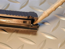 The chisel end of the tool can be used to pull the 1911 extractor from the slide without scratching the finish.