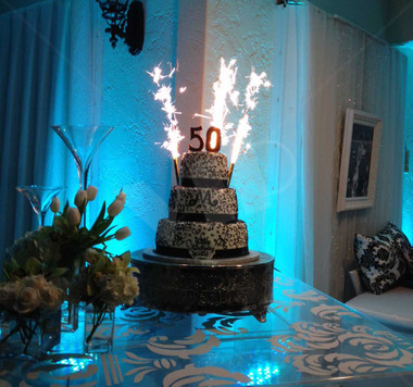 Celebrate your wedding, anniversary or birthday with silver party candle sparklers. Displayed in picture is a tiered wedding cake with candle sparklers lit setting on a table.