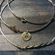 Heavy 14kgf gauge hammered bangles. One of them has a single lowercase initial charm.