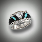 R 801 center stone is a 6mm trillion cut renzite with 18 points of F/VS pave` diamonds hand carved pieces of turquoise and black jade inlay set in 14kt white gold.