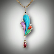 IP 29 multicolored pendant has hand carved pieces of turquoise, phosphosiderite, variscite, and coral with 12 pts pave` F/VS diamonds with a 8mm marquise cut rhodolite cabochon stone all hanging from a pave' diamond bail set in 14kt yellow gold.