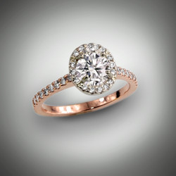 This custom engagement ring has a 0.91ct oval brilliant H/SI2 center stone with a halo of 24 pave` F/VS diamonds of 16 points all set in white gold.  The band has 18 pave` F/VS of 12 points set in 14kt rose gold.