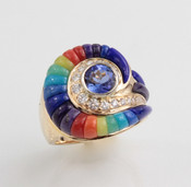R 539 has a round 6.5mm tanzanite surrounded by 20 round pave` F color VS clarity diamonds with swirls of lapis, lavulite, turquoise, coral, light chrysoprase, and verde antique, that resembles the look of a escargot shell set in 14kt yellow gold.