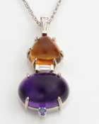 This pendant has a triangle shaped citrine cabochon on top of a baguette diamond with a oval amethyst cabochon with a blue sapphire on the bottom.  The pendant is set in a 14kt white gold frame with a baguette diamond on the bail.