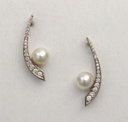 ER-Pearl earrings have a 7mm white Akoya pearl set off the side of a row of 26.75 total points pave` F/VS diamonds set in 14kt white gold.